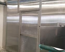 Cloisons en Inox 304 et panneaux alvéolé transparent pour laisser passer la lumière. Porte réalisée sur-mesure.